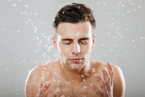 Ein Mann spritzt sich Wasser ins Gesicht