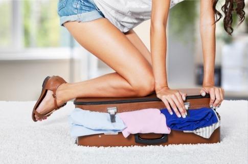 Eine Frau kniet auf ihrem Koffer