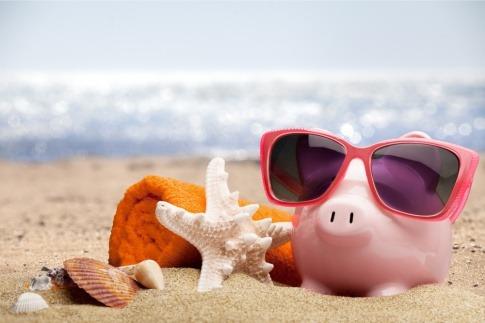 Ein Sparschwein ist auf einem Strand und Utensilien zum Reisen