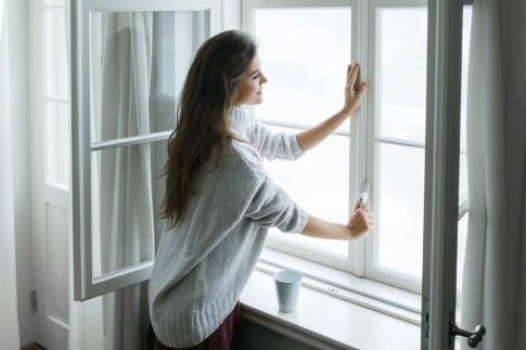 Eine Frau öffnet ein Fenster um richtig zu lüften