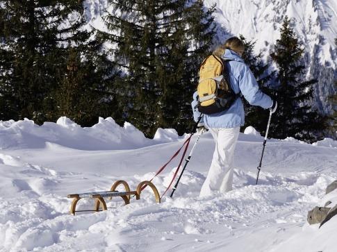 Eine Frau geht mit einer Rodel durch den Schnee