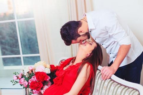 Ein Mann tritt von hinten an seine auf dem Sofa sitzende Partnerin heran und küsst sie von oben.