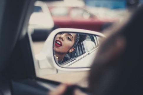 Eine Frau trägt sich im Auto roten Lippenstift auf