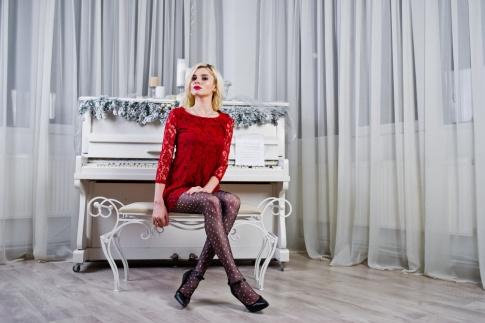Ein blondes Model in einem eleganten roten Kleid sitzt vor einem weihnachtlich dekorierten Hintergrund auf einem Pianohocker.