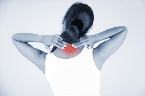 Eine Frau ist von hinten abgebildet, sie greift sich mit den Händen auf Nackenbereich. Die Farben des Fotos sind grau, nur der Nacken ist rot eingefärbt.