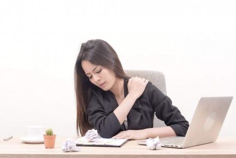 Eine am Schreibtisch sitzende Frau greift sich mit schmerzverzerrtem Gesicht an die Schulter. Rückenschmerzen, Homeoffice und eine fehlende Routine bei der Heimarbeit hängen oft miteinander zusammen.