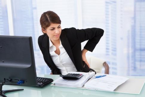 Eine Frau sitzt beim Schreibtisch und hat Rückenschmerzen