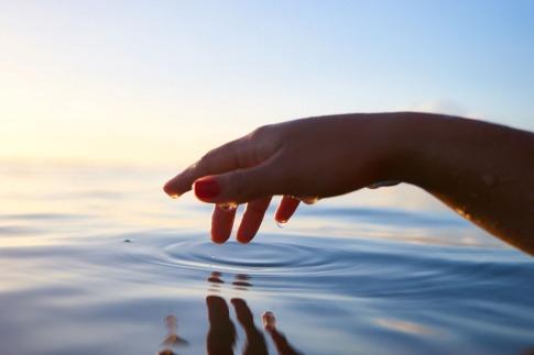 Ruhige Kreise im Wasser werden durch einen Finger gezogen