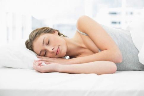 Frau schläft entspannt, weil keine Störfaktoren im Schlafzimmer sind