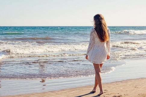 Frau mit langen Haaren am Strand neben Salzwasser