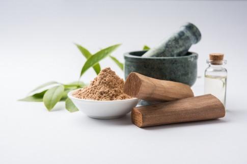 Das Chandan- oder Sandelholzpulver mit traditionellem Mörser, Sandelholzstäbchen und Öl sind neben grünen Blättern platziert