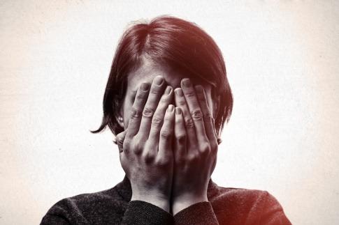 Eine Frau, die Probleme mit dem Scham überwinden hat, bedeckt ihr Gesicht mit ihren Händen.