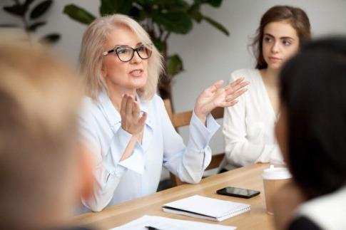 Eine ältere Frau diskutiert mit anderen Menschen an einem großen Tisch.