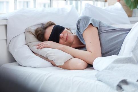 Eine Frau im Bett trägt eine Schlafmaske für erholsamen Schlaf