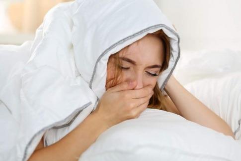 Eine Frau unter einer Decke gehnt und hat offensichtlich Schlafprobleme