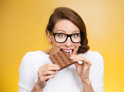 Eine Frau beißt in eine Tafel Schokolade und scheint keine Angst vor schlechter Haut zu haben