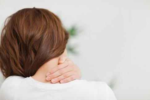 Frau mit Schmerzen im Nacken