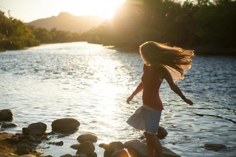 Eine Frau steht ohne Schmerzen im Wasser und wirkt glücklich