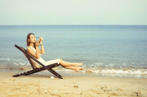 Frau schminkt sich am Strand