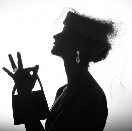 Eine Frau mit glamourösen Make-up und Hairstyling trägt einen pompösen individuellen Schmuck