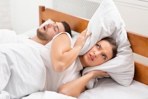 Ein Mann schnarcht neben einer Frau und sollte es behandeln lassen
