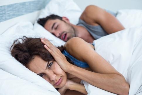 Ob Gurgeln gegen Schnarchen dieser Frau hilft, ihrem Partner das lästige problem abzugewöhnen? Sie liegt im Bett und hält sich die Ohren zu.