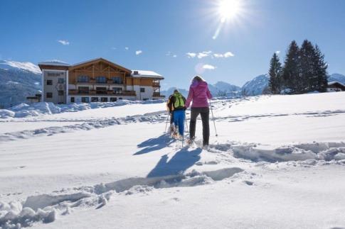 Eine Gruppe Menschen macht bei einer Schneeschuhwanderung mit