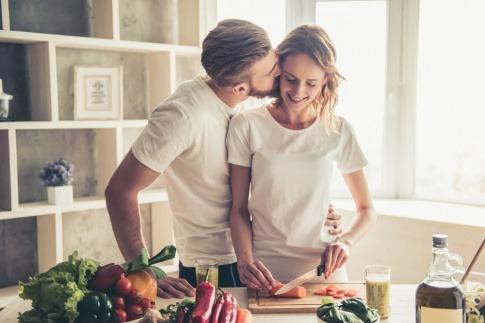 Ein Mann küsst eine Frau, die Abendessen kocht