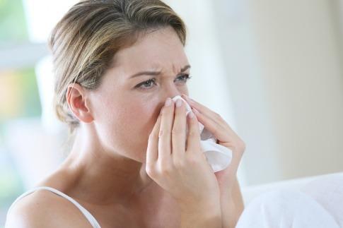 Eine Frau mit Schnupfen hat ein Taschentuch auf der Nase