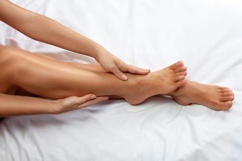 Eine Frau hält gepflegte Beine und Füße