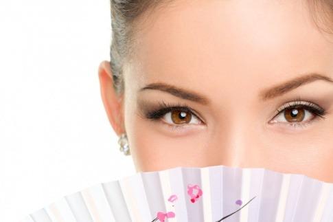 Frau hinter asiatischem Fächer mit schöner Haut