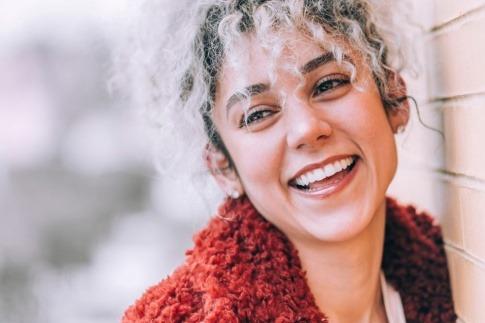 Eine Frau hat schöne Zähne durch Zahnersatz und lächelt