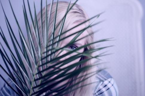 Wer Schüchternheit überwinden möchte, muss wie die Frau, die in diesem Bild verstohlen hinter einer Pflanze hervorschaut, an seinem Selbstbewusstsein arbeiten.