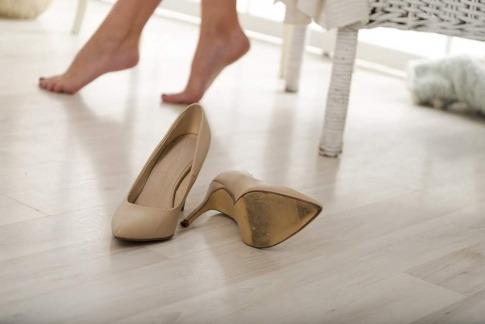 Neben einer Frau liegen Schuhe, die Schuld an Rückenschmerzen sein können