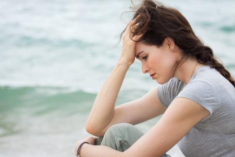 Eine Frau sitzt auf einer Düne am Strand, der Kopf ist nach unten gesenkt, ihr Ausdruck wirkt traurig und ratlos.