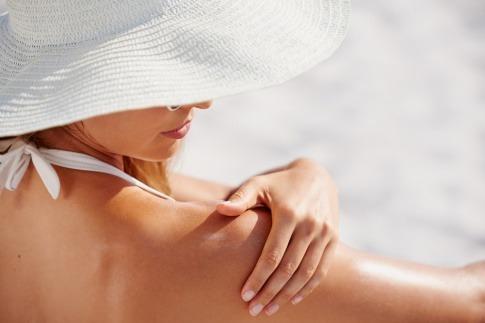 Eine Frau cremt Ihre Schulter mit Sonnenschutz ein