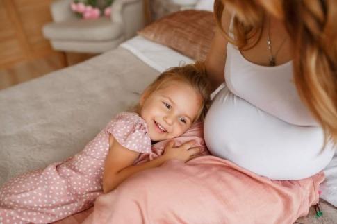 Ein Kind lehnt am Bauch einer schwangeren Frau