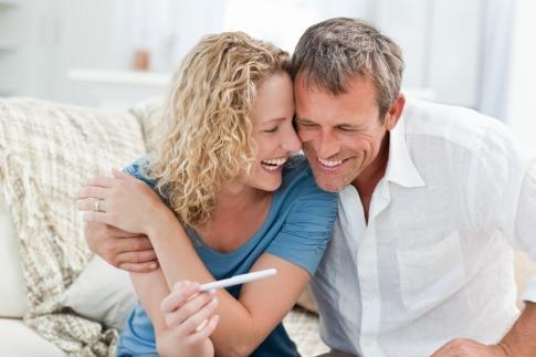 Eine Frau und ein Mann sitzen am Bett mit einem Schwangerschaftsstreifen und wollen schwanger werden