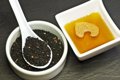 Schwarzkümmelöl ist in einer Schüssel neben Samen des Schwarzkümmels