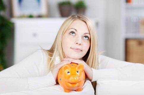 Eine junge blondhaarige Frau sitzt auf einem weißen Sofa. Mit ihren Handflächen formt sie ein Dach, darunter steht ein Sparschwein. Die Frau blickt hoffnungsvoll nach oben.