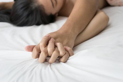 Eine Frau und ein Mann liegen im Bett und haben Sex