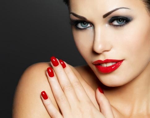 Eine Frau blickt verführerisch, hat rote Lippen und im selben Farbton die Fingernägel lackiert. Es handelt sich um eine Großaufnahme ihres Gesichtes.