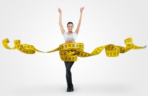 Eine schlanke Frau ist in der Mitte des Bildes abgebildet. Um sie herum schlängelt sich ein gelbes Maßband in überdimensionalem Maße. Sie hat die Arme in die Höhe gestreckt und lächelt.