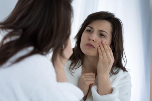 Eine Frau blickt in den Spiegel und betrachtet ihre müde, fahle Haut. Sie hat braune Haare, braune Augen und trägt einen weißen Bademantel.