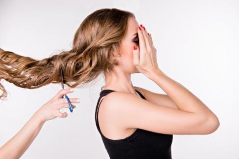 Haare einer Frau werden geschnitten, sie hält die Hände vor das Gesicht