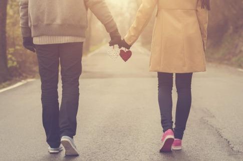 Ein Paar, das Hand in Hand mit jeweils einem Herz in der Hand einen Spaziergang macht