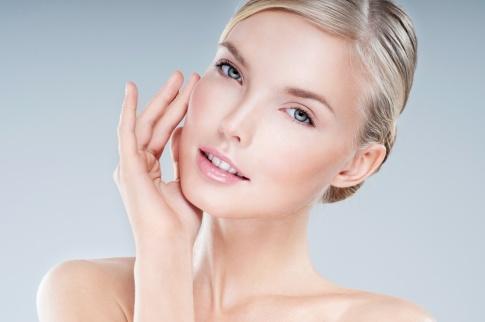Das Gesicht einer blonden Frau ist abgebildet. Sie hat sehr schöne Haut. Ihre Augen sind grün-grau. Sie lächelt leicht in die Kamera.
