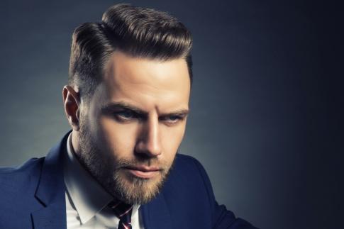 Ein Mann mit kurzen brünetten Haaren und blauem Anzug