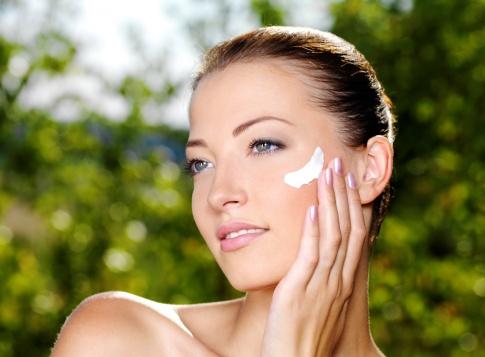 Frau pflegt sonnengestresste Haut mit Balance Creme