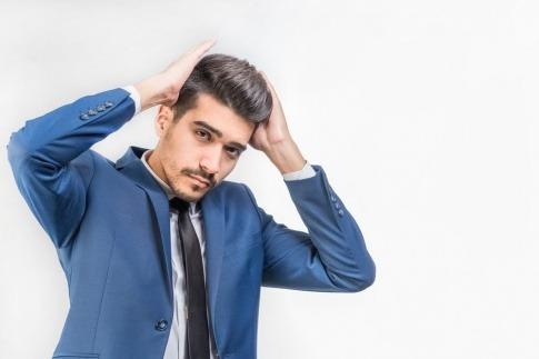Ein Mann mit hoch gestyltem dunklem Haar hebt sich beide Hände ins Haar